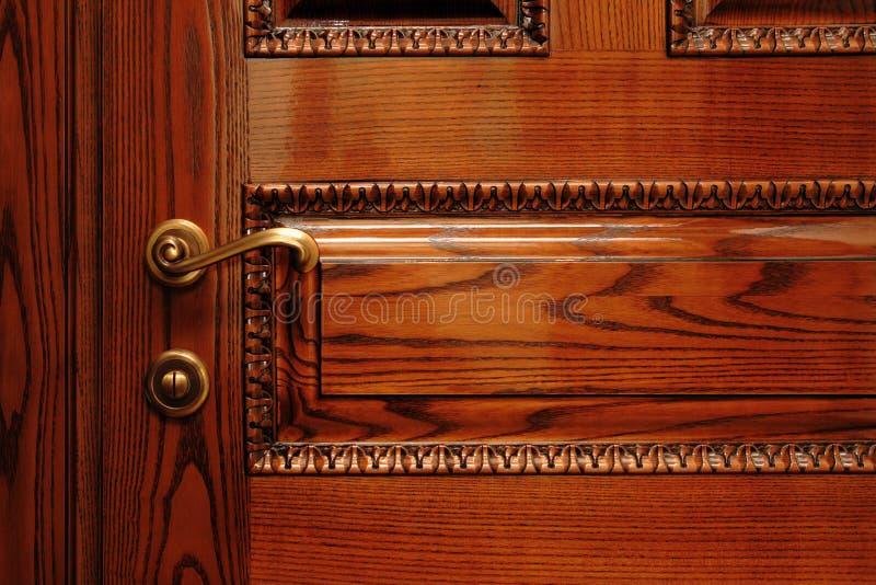 Door handle on the wooden door royalty free stock photography