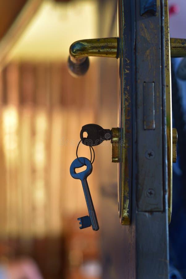 Door key hanging on the key hole stock image