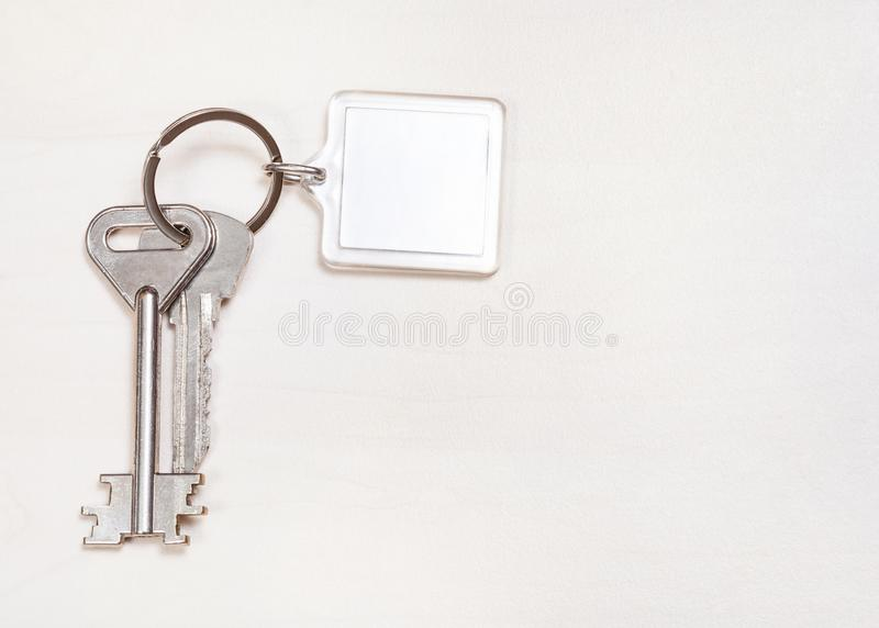 Door keys on keyring with blank white keychain. On pale brown table royalty free stock photography