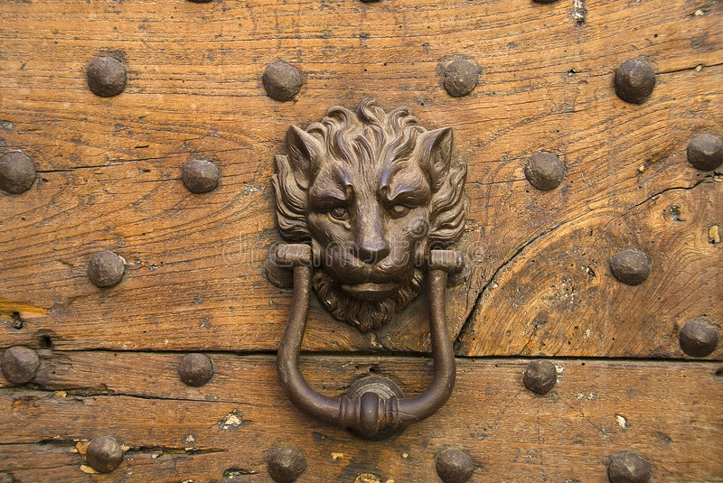 Door-knocker. Old door-knocker in the shape of a lionhead at wooden door with rivets in Rome royalty free stock image