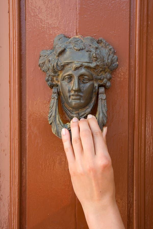 Door knocker. Old door knocker with ladies hand. Wooden door stock photography