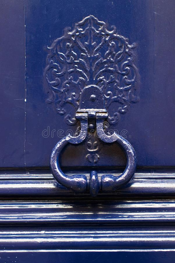 Door knocker on a blue wooden door stock photo