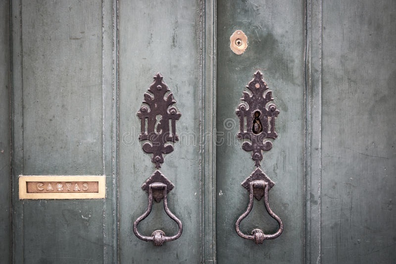 Door knockers, lock and a mailbox of an ancient green wooden door. Ancient door knockers, lock and a mailbox of an ancient green wooden door royalty free stock image