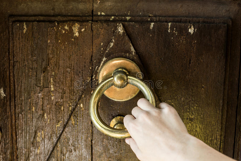 Door knocking. Hand is knocking the old door, knocker royalty free stock images