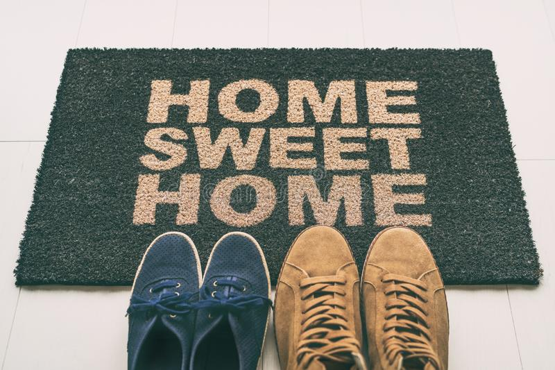 Door mat Shoes at front entrance of condo apartment. Written welcome sign Home Sweet Home welcoming homeowners at new house moving stock images