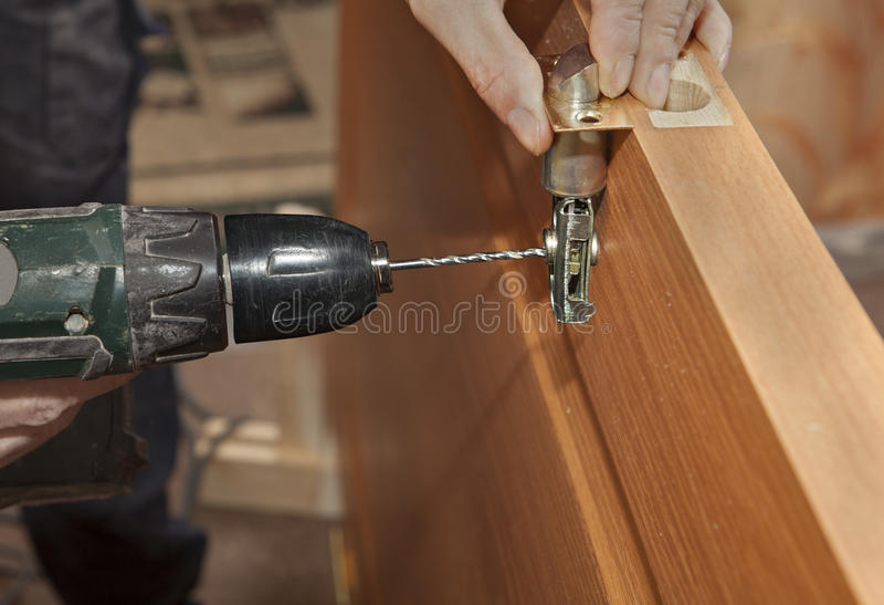 Door mounting, install deadbolt lock, electric drill drilled hole, close-up. stock photos