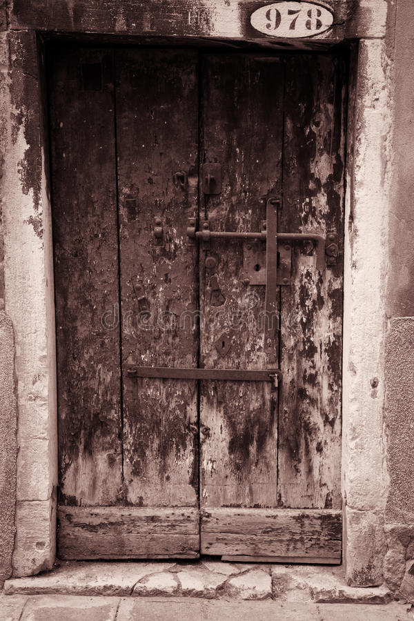 Door 978. Old rustic door in sepia has stood the test of time. Hand carved stone work surrounds the aging door. Simple wrought iron latches and hardware adorn royalty free stock images