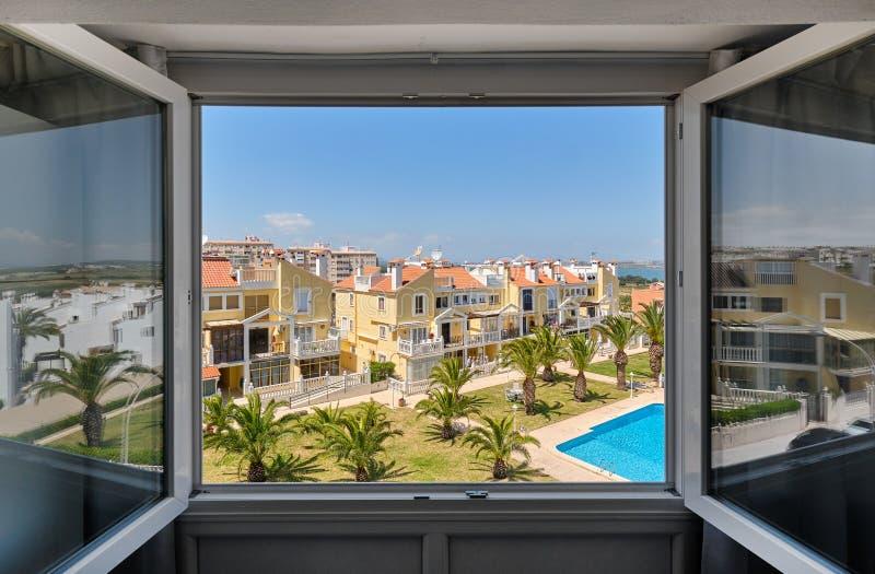 Door open venstermening aan gesloten gebied van urbanisatie met geplante palmen op groen gazon rond zwembad met blauw water royalty-vrije stock afbeelding