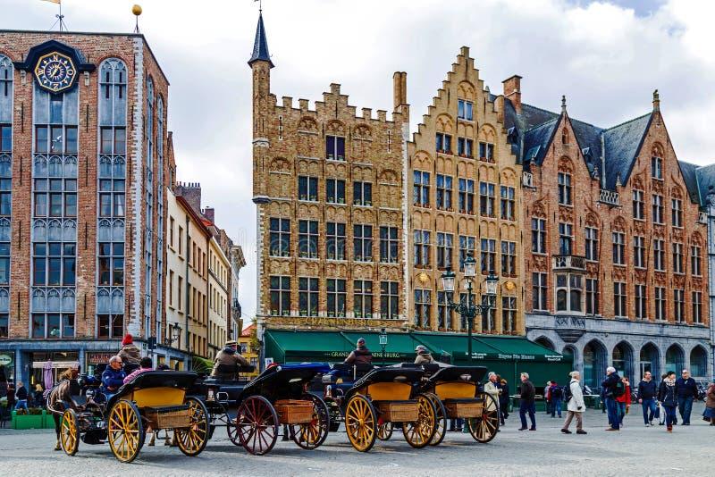Door paarden getrokken vervoer met toeristen in Grote Markt, Brugge, Belgi stock afbeelding