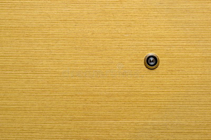 Door peephole for review. Fragment of a yellow wooden door with a peephole for use as a background royalty free stock images