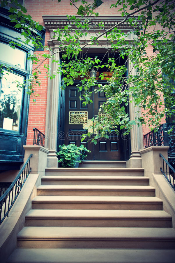 Door and Stairs of Greenwich Village Townhouse. Green Tree Branch in front of Door and Stairs on Exterior of Upscale Townhouse in Greenwich Village, New York stock photos