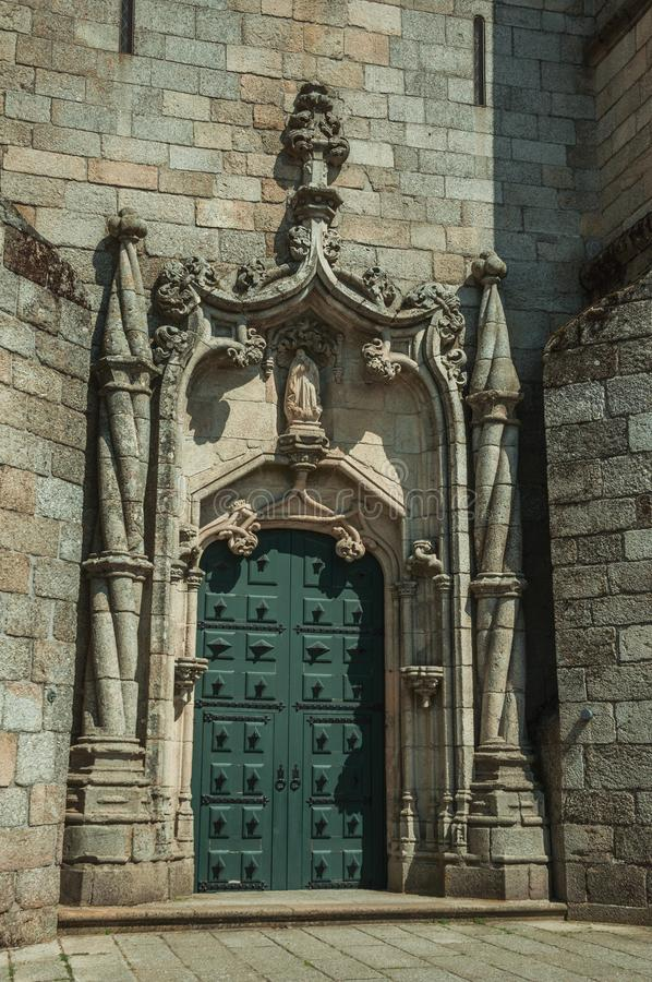 Door and stone decoration spiraling column in a Cathedral. Wooden door and stone decoration with typical Manueline spiraling column, at the facade of Guarda stock image