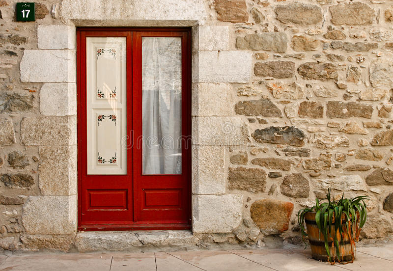 Door of a stone house and a flowerpot, Spain royalty free stock photography