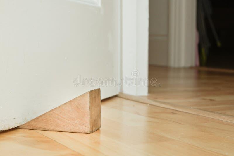 Door stopper. A wooden door stopper on a laminate floor royalty free stock image