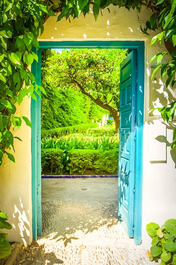 Door to garden with orange tree. Door leading in patio, so called andalusian cortyard , Cordoba, Spain , toned royalty free stock image
