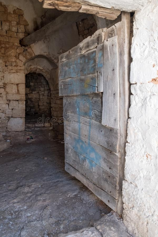 Door to the interior of a neglected conical roofed Trullo house in Alberobello, Puglia Italy. stock image