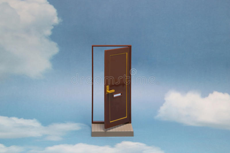 Door to new world. Open door on blue sunny sky with fluffy clouds. Concepts like new life, success, future perspective, hope, religion stock photography