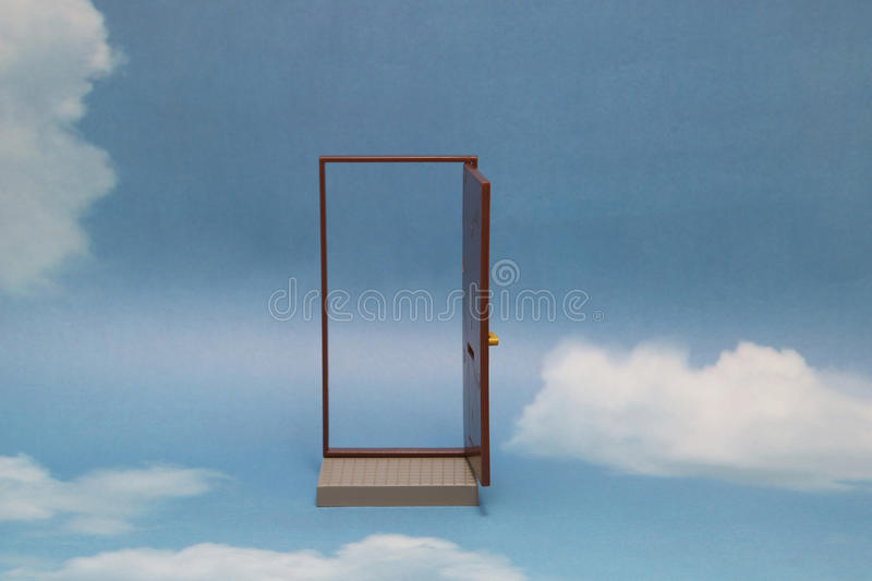 Door to new world. Open door on blue sunny sky with fluffy clouds. Concepts like new life, success, future perspective, hope, religion stock image