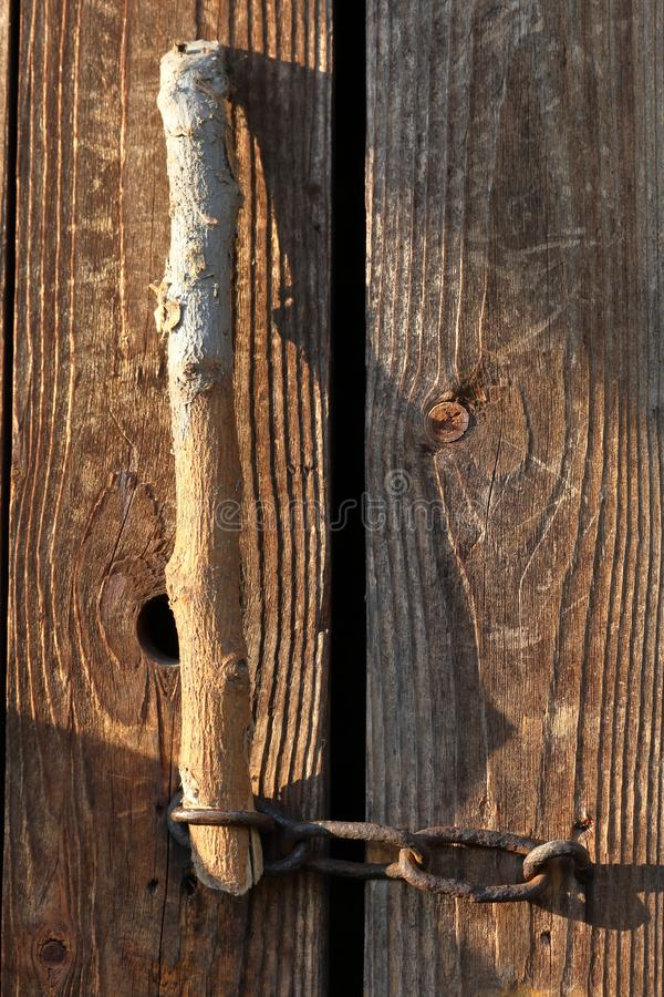 The door to the old barn is closed on a chain. A wooden stick is inserted into the loop royalty free stock images