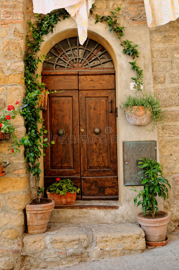 Door to Tuscan house. Decorative wooden door to a stone house or building in Tuscany, Italy stock photos