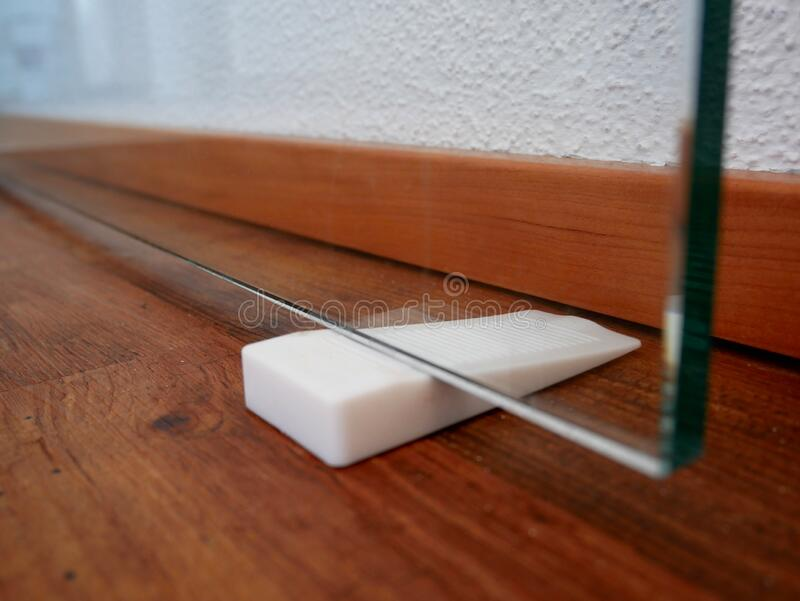 Door white plastic stopper sticked into glass doors royalty free stock photos