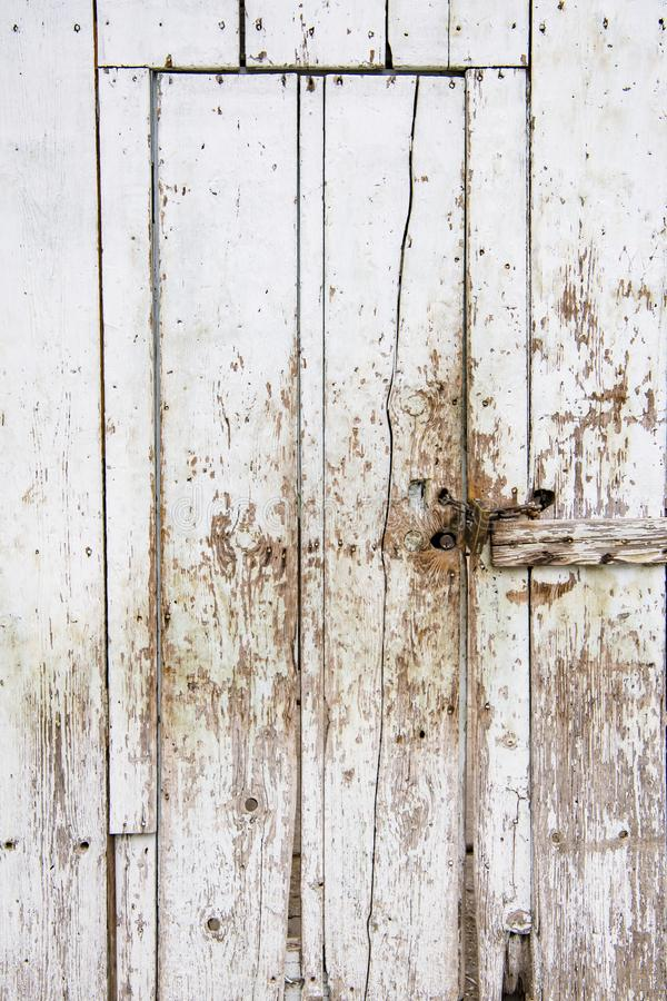 Door in wooden plank wall with peeling white color royalty free stock photo