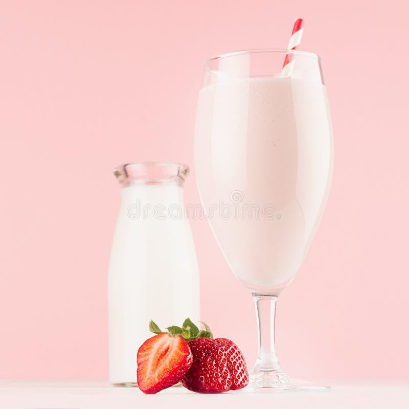 Doorboren de de zomer koude verse zuivelcocktail met melkfles, de heldere aardbei, het stro op witte houten raad en de leuke zach royalty-vrije stock afbeeldingen