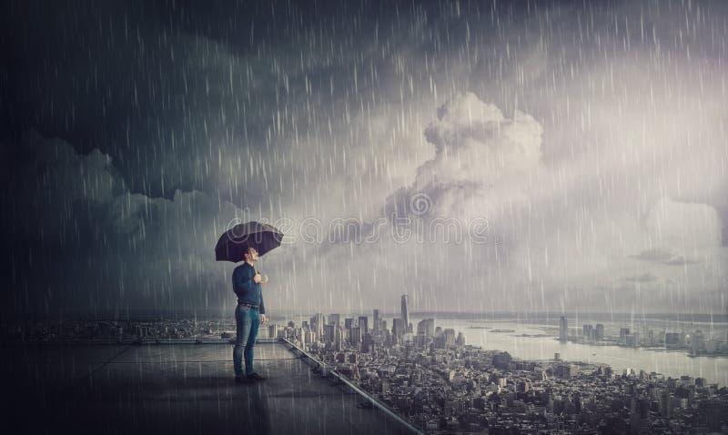 Doordacht zakenman die onder storm staat op de daken van een wolkenkrabber die de horizon van de stad bekijkt Bedrijfsonderzoeksc royalty-vrije stock afbeelding