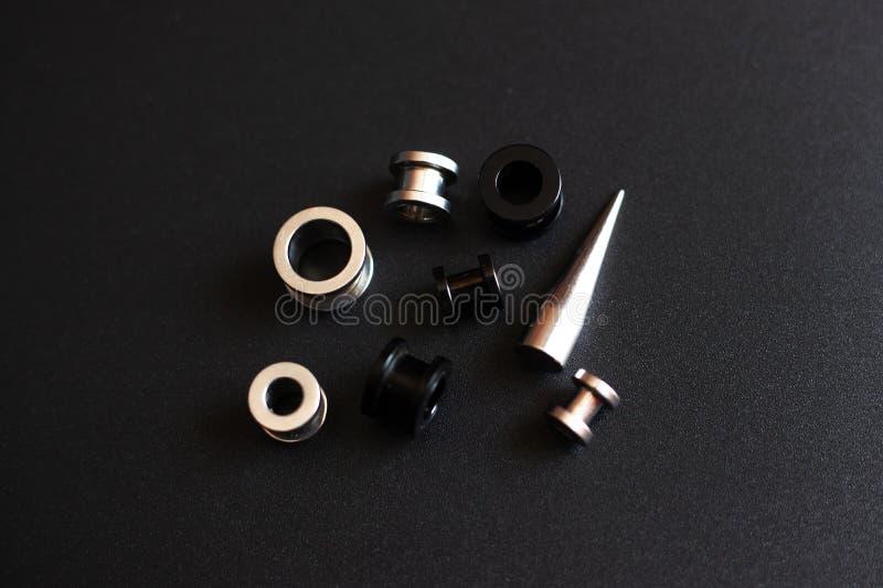 Doordringende toebehoren op zwarte achtergrond roestvrije metaaljuwelen voor punctuurminnaars stock afbeelding