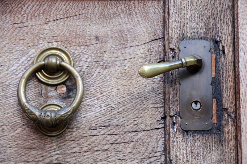 Doorknob and knocker on old wooden door stock images