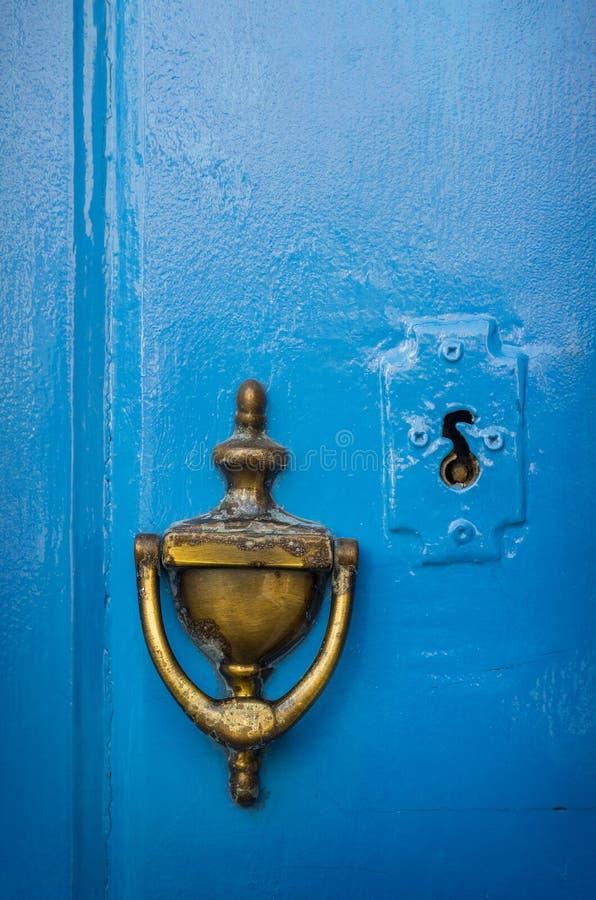 Doorknob. Old brass doorknob and keyhole in a blue door royalty free stock photo