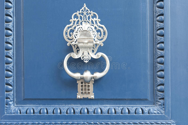 Doorknocker blanco en una puerta azul fotografía de archivo
