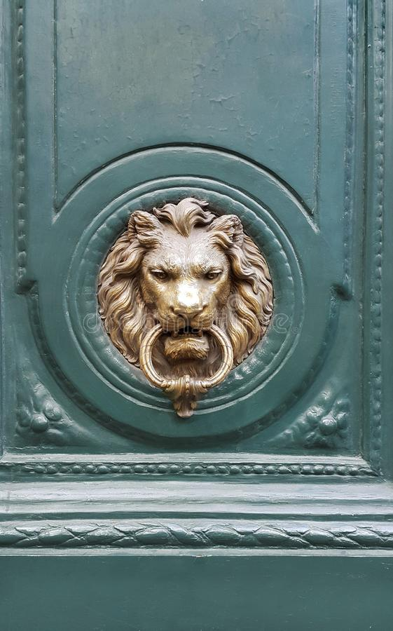 Doorknocker with head of lion on a green wooden door royalty free stock photo