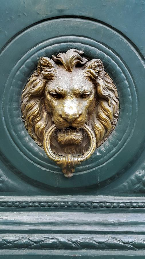 Doorknocker with head of lion on a green wooden door stock photos