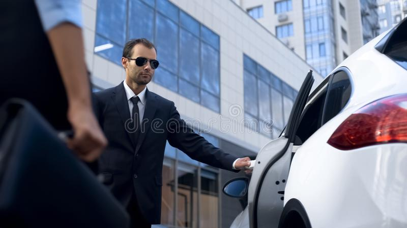 Doorman of business centre opening car door to lady businesspeople accompaniment royalty free stock images