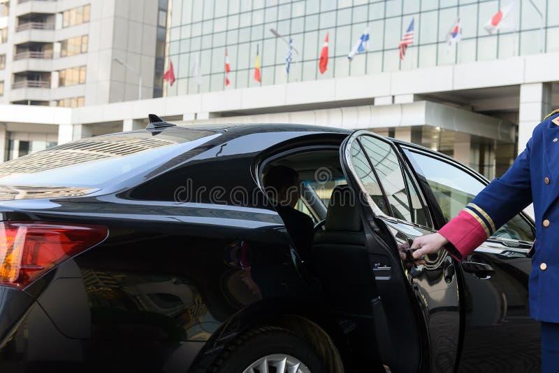 Doorman otwiera drzwi luksusowy samochód zdjęcia royalty free