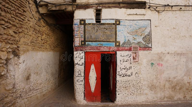Doors in the Fes, Morocco. Red doors in Fes, Morocco on small street in old part. White wall with arabic words stock photography