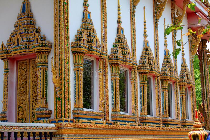 Doors and windows of the temple adorned by intricate wooden carvings in golden color depicting Buddha`s life familiarized by Jata stock photography