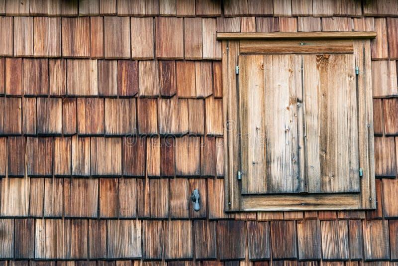 Doorstaan en langzaam verdwenen van de zon houten dakspanen die de voorgevel van een alpien huis zijn Houten textuur in schaduwen stock foto