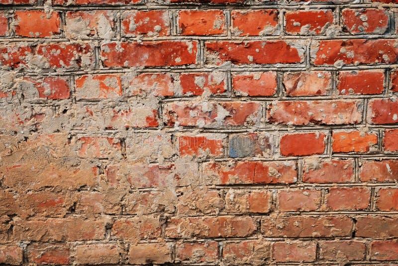 Doorstane Bevlekte Oude half gepleisterde Bakstenen muur stock afbeelding