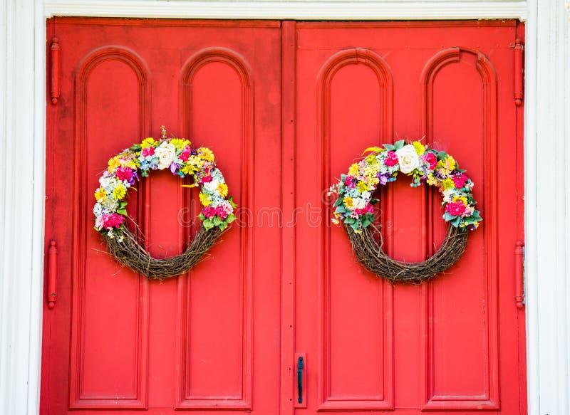 Doorstane heldere rode kerkdeur met bloemkronen stock fotografie