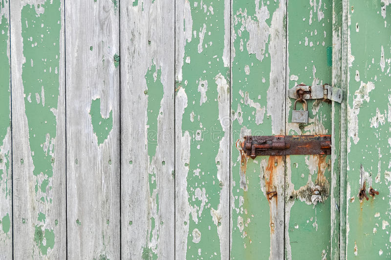 Doorstane houten deur die groene verf pellen stock afbeelding
