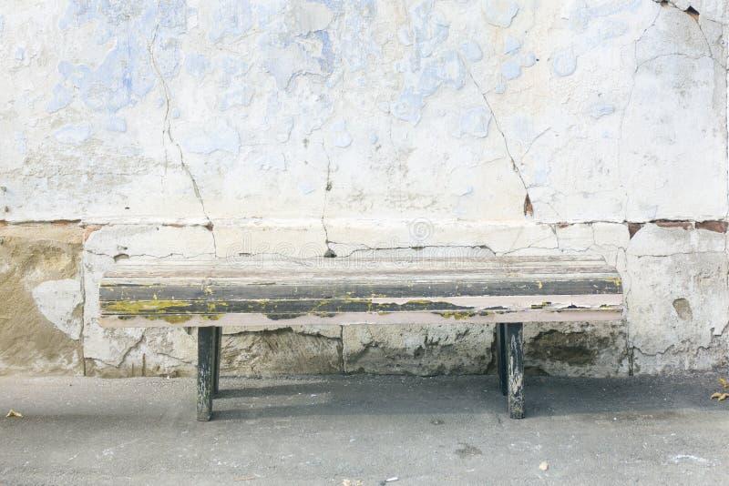 Doorstane oude oude houten bank De vernietigde grunge blauwe achtergrond van de pleistermuur royalty-vrije stock afbeeldingen