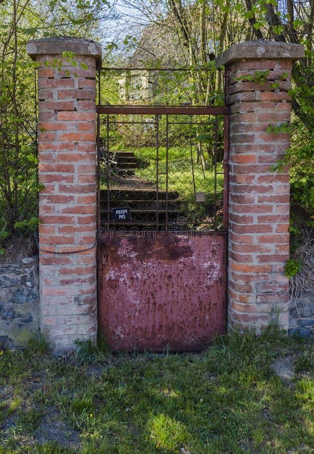 Doorstane oude roestige tuinpoort, met teken in Tsjech, die betekent: Voorzichtig zijn van Hond royalty-vrije stock fotografie