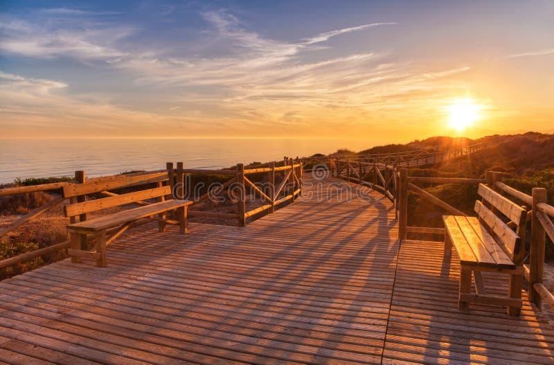 Doorstane timmerhoutweg die tot kalme overzees tijdens mooie zonsondergang leiden royalty-vrije stock afbeelding
