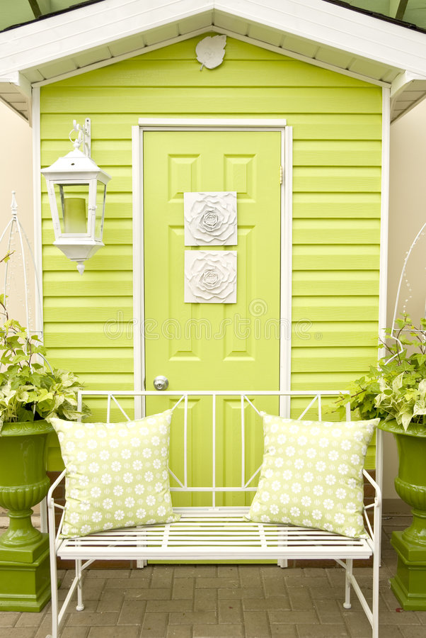 Doorway and Patio Furniture. Vibrant lime green door and patio furniture with matching pillows stock image