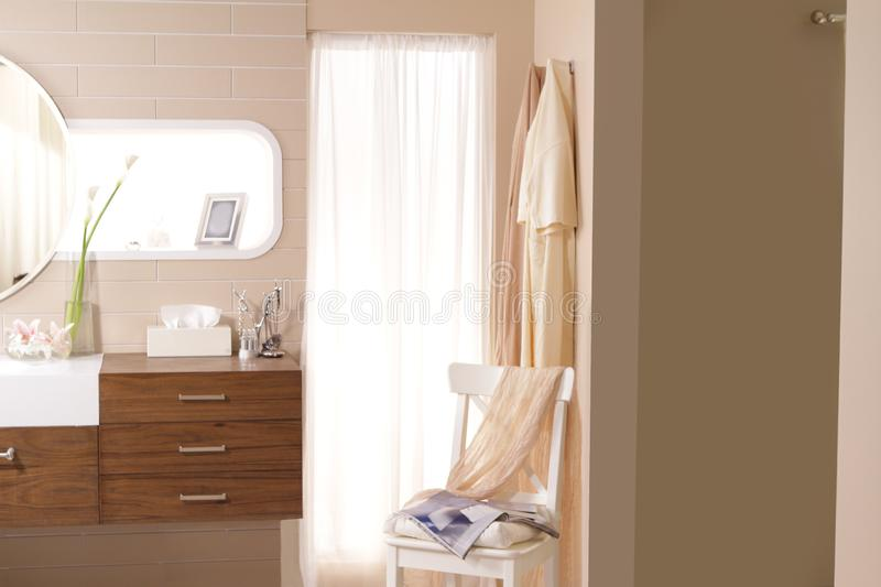Doorway to the bathroom. There are a magazine and some cloths put on the chair and hanging on the wall at doorway to bathroom stock image