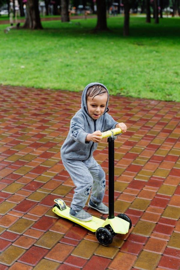 Doorweekt in de regen, schaatst een jongen in een sportkostuum op een autoped De lentegang in het stadspark, regenachtig weer royalty-vrije stock afbeeldingen
