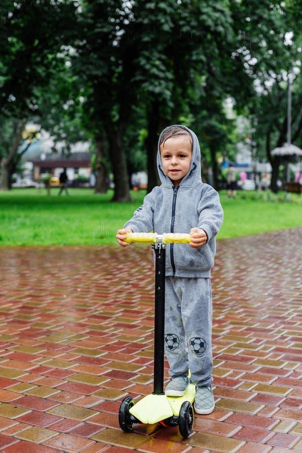 Doorweekt in de regen, schaatst een jongen in een sportkostuum op een autoped De lentegang in het stadspark, regenachtig weer stock afbeelding