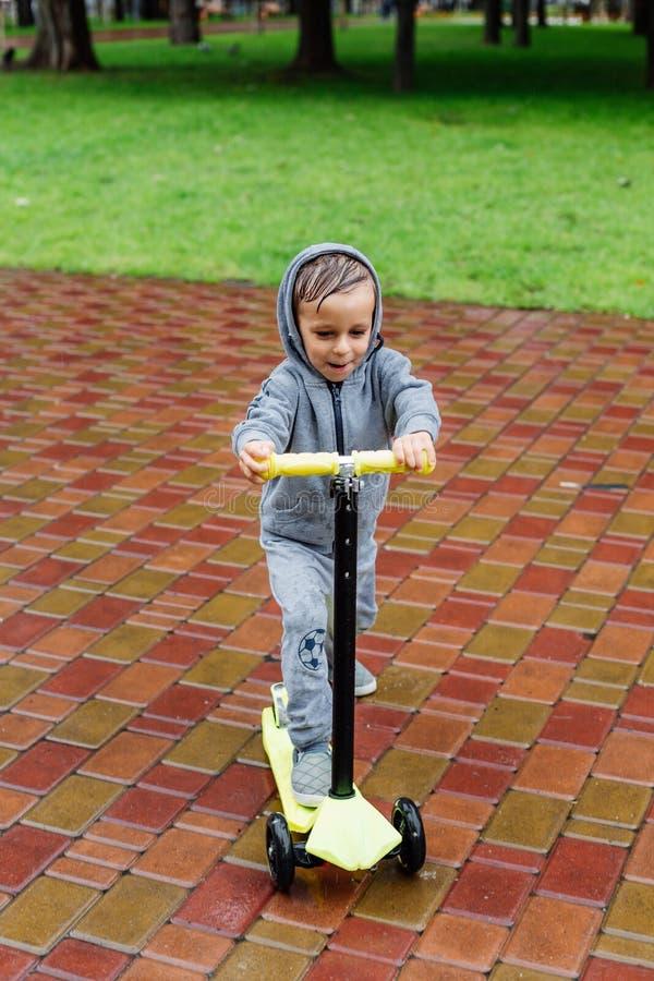 Doorweekt in de regen, schaatst een jongen in een sportkostuum op een autoped De lentegang in het stadspark, regenachtig weer stock foto's